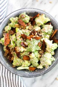 ThisHealthy Vegan Broccoli Salad is an easy recipe that is BIG on flavor. Broccoli is coated in a sweet and creamy dressing and jazzed up with smokey coconut bacon, toasty seeds, and sweet raisins. | CatchingSeeds.com