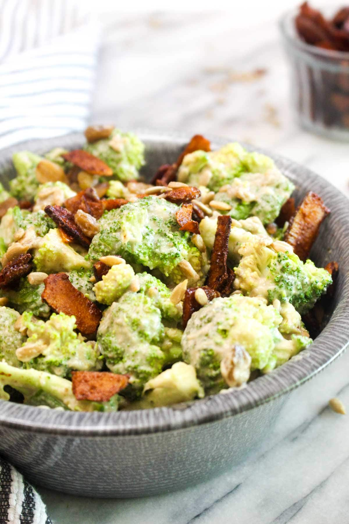 This Healthy Vegan Broccoli Salad is an easy recipe that is BIG on flavor. Broccoli is coated in a sweet and creamy dressing and jazzed up with smokey coconut bacon, toasty seeds, and sweet raisins. | CatchingSeeds.com