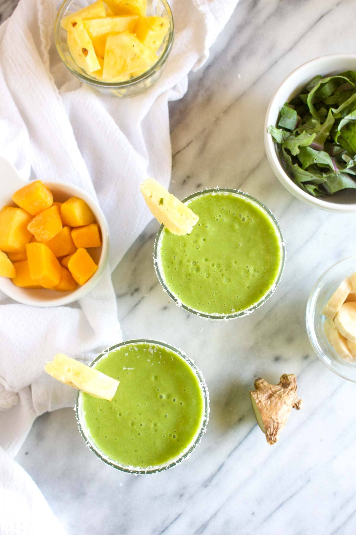 Tropi Kale Smoothie is a 10 minute recipe that is packed with tropical flavors. 6 simple and healthy ingredients make this an easy grab and go breakfast.   CatchingSeeds.com
