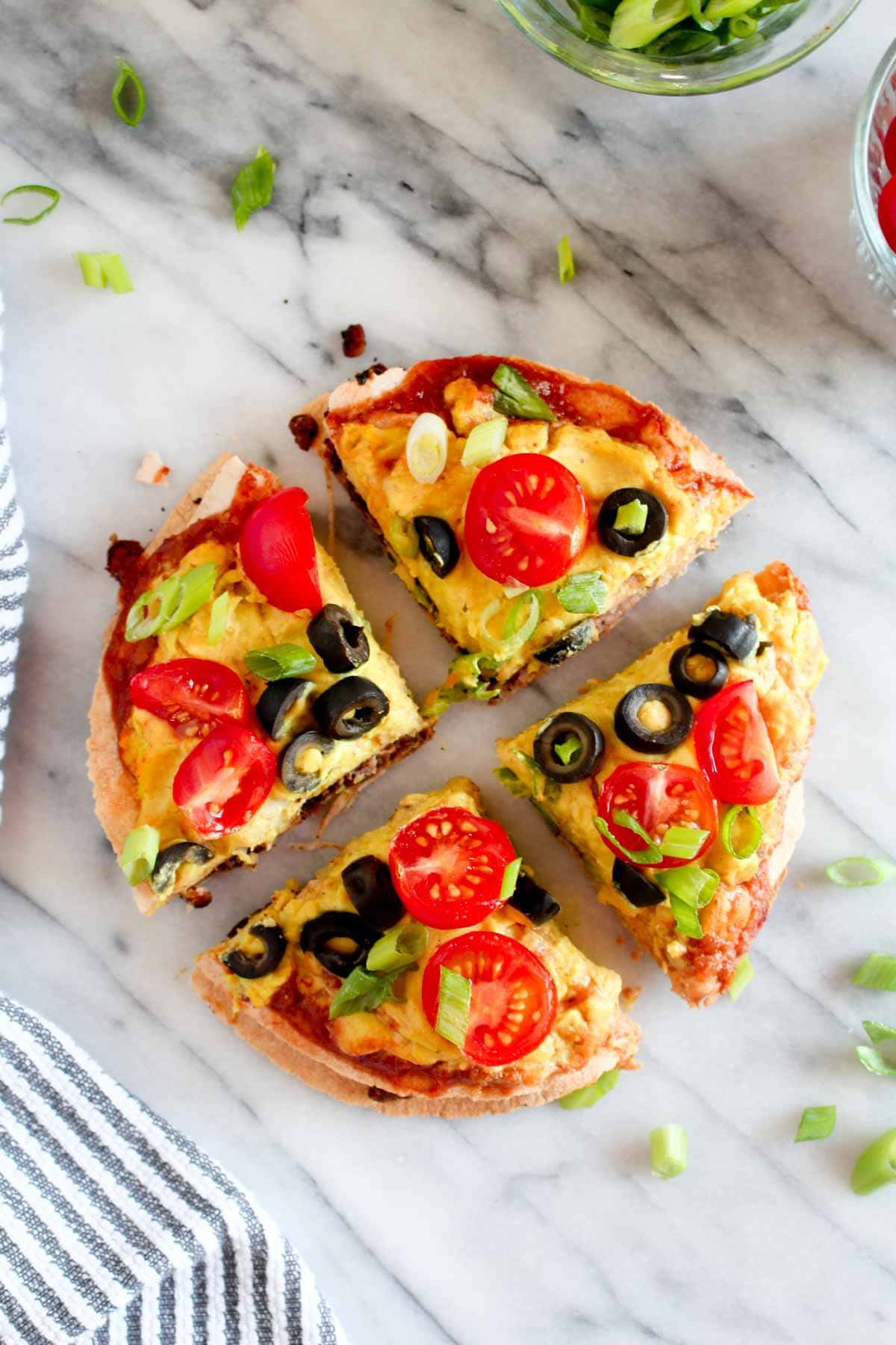 This Mexican Tortilla Pizza is double decker masterpiece filled with creamy beans, tempeh taco meat, and lots of cheese. A perfect healthy weeknight recipe. | CatchingSeeds.com