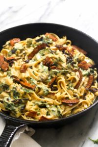 This Vegan Pumpkin Alfredo with Glazed Shiitakes and Coconut Bacon is a Fall dish packed with flavor. No one will know its healthy and gluten-free. | CatchingSeeds.com