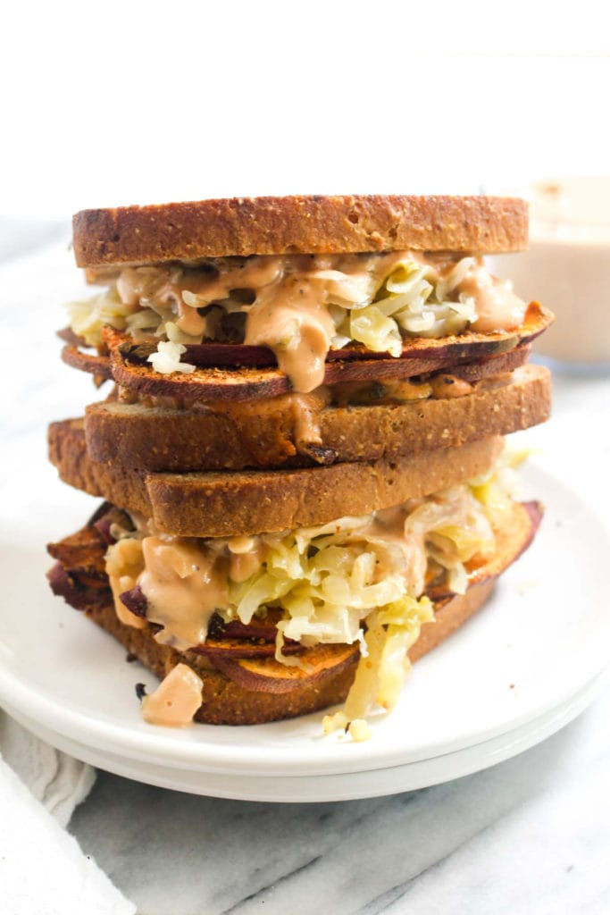 This Sweet Potato Pastrami Reuben Sandwich recipe is a vegan revelation! It is warm, melty, golden-brown and has all the flavors of your favorite sandwich.   CatchingSeeds.com