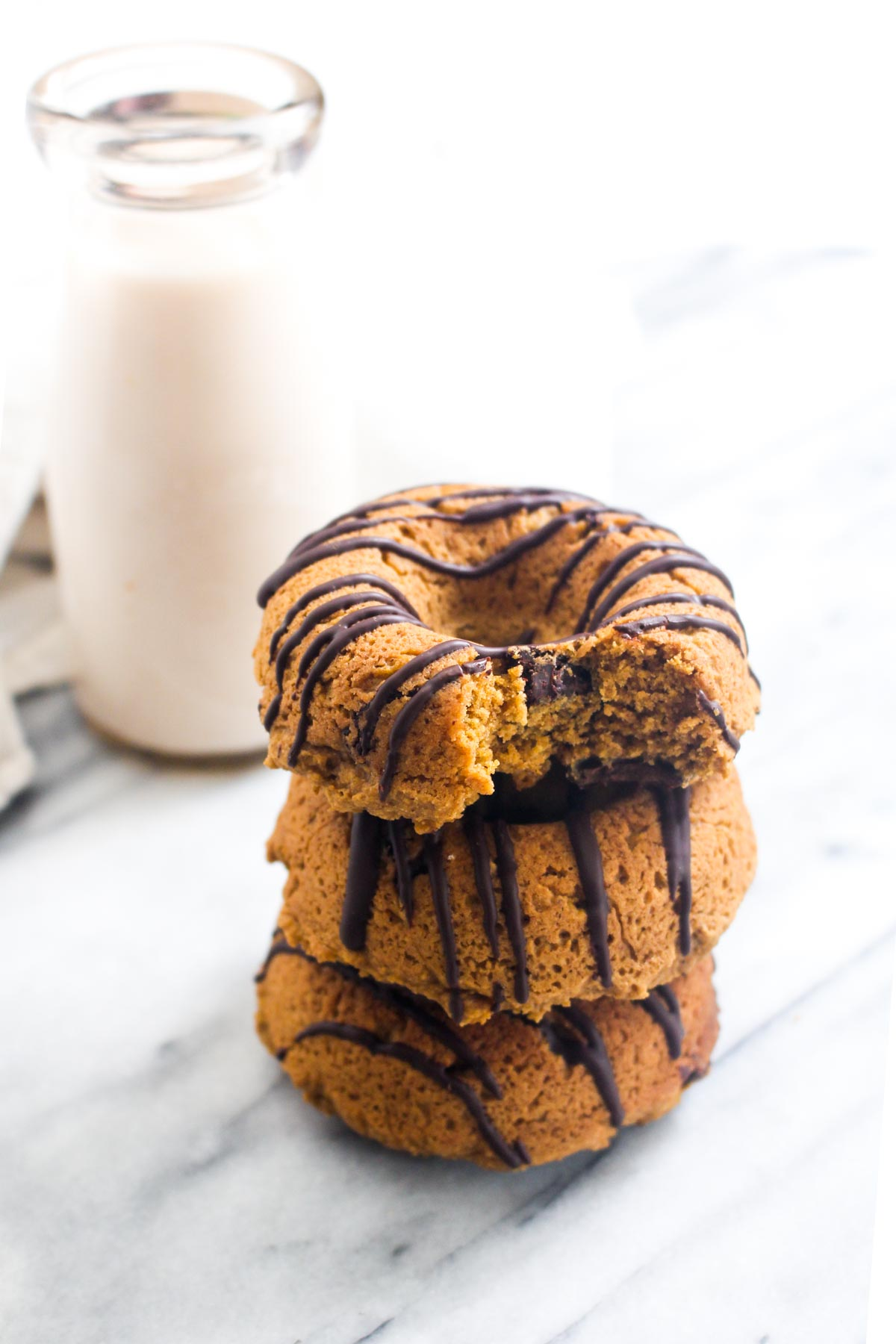 These Pumpkin Chocolate Chip Donuts are a secretly healthy dessert! They are gluten-free, vegan, and made with natural sweeteners. | CatchingSeeds.com