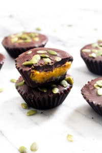 These Pumpkin Caramel Chocolate Cups are a simple no-bake Fall dessert recipe! Dark chocolate envelopes silky smooth pumpkin caramel. | CatchingSeeds.com