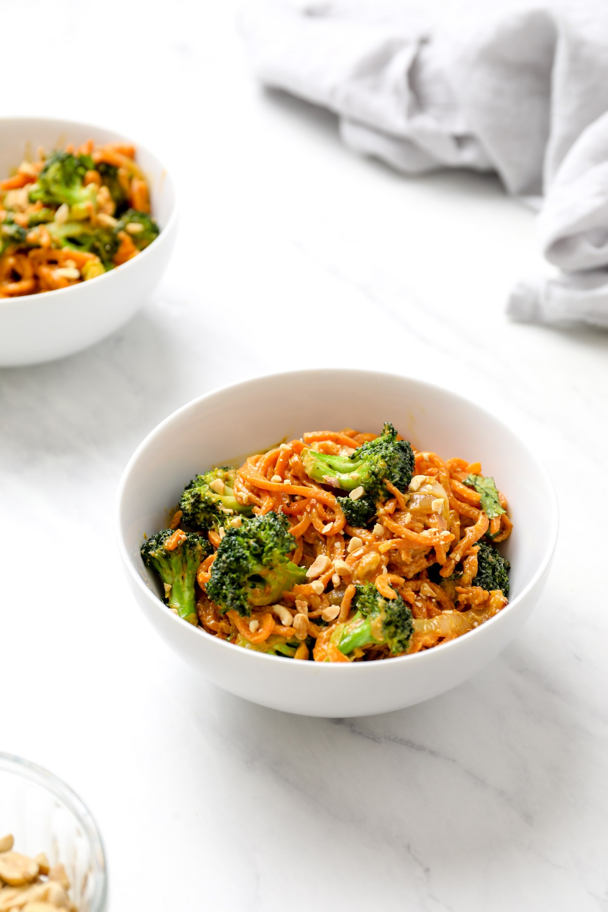 Two bowls of Peanut Sauce Sweet Potato Noodles with broccoli.