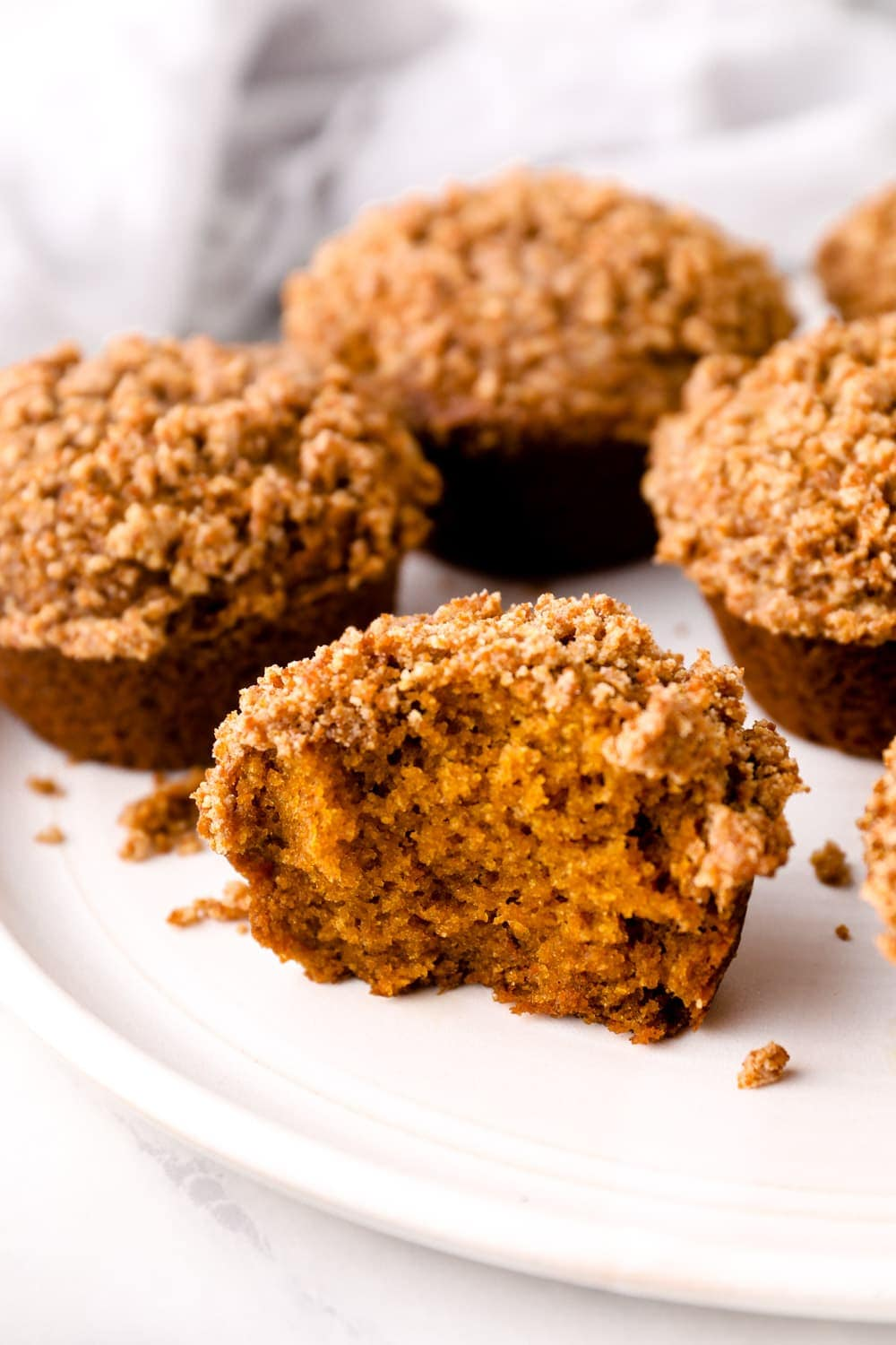 A Gluten Free Pumpkin Muffin cut in half and topped with crumble.