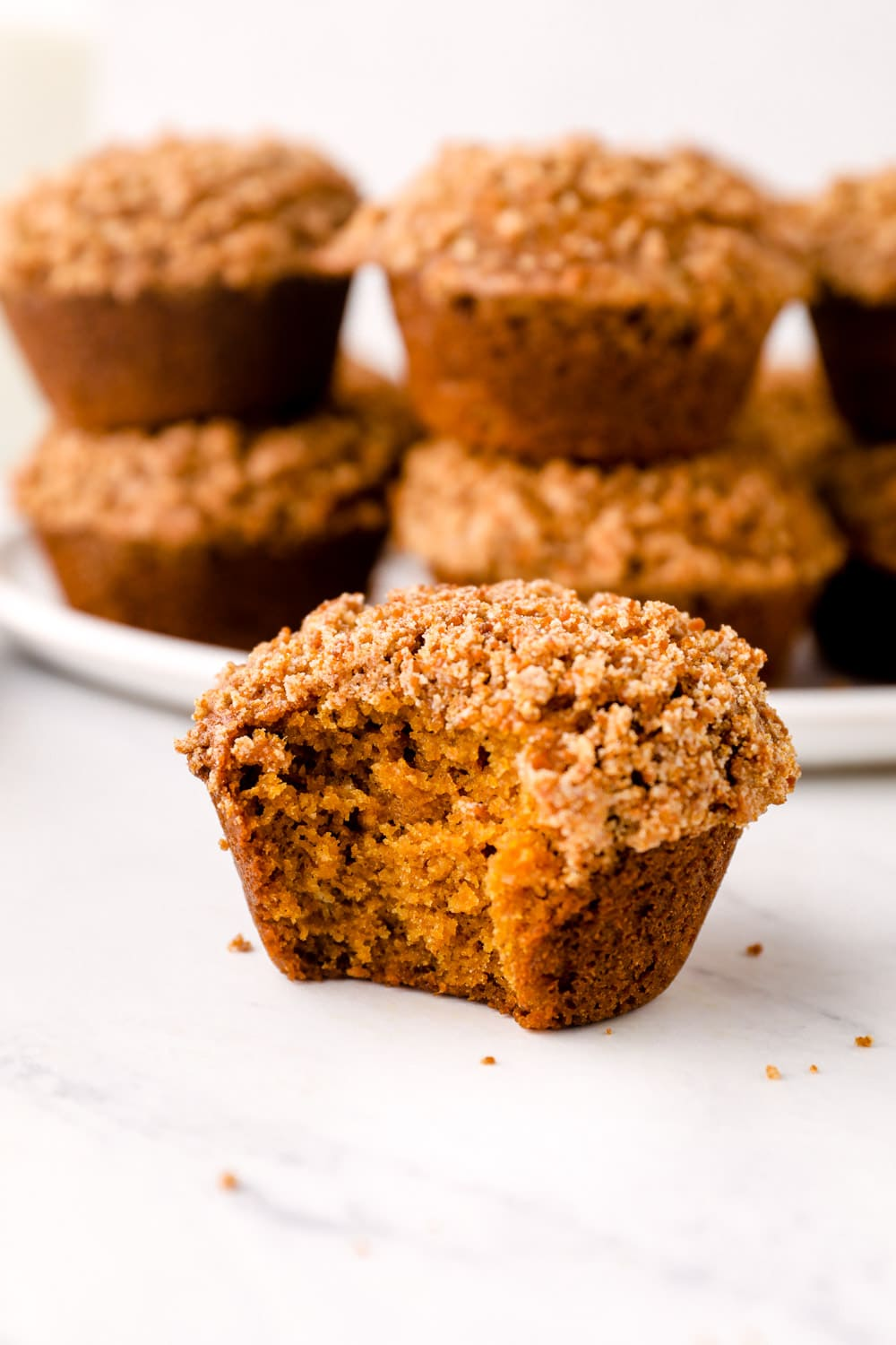 A bite out of a Gluten Free Pumpkin Muffin with crumb topping.
