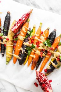 This 7 ingredientWhole Roasted Carrots with Maple Tahini recipe is easy to make but boasts BIG flavors. This light side dish is paleo and vegan! | CatchingSeeds.com