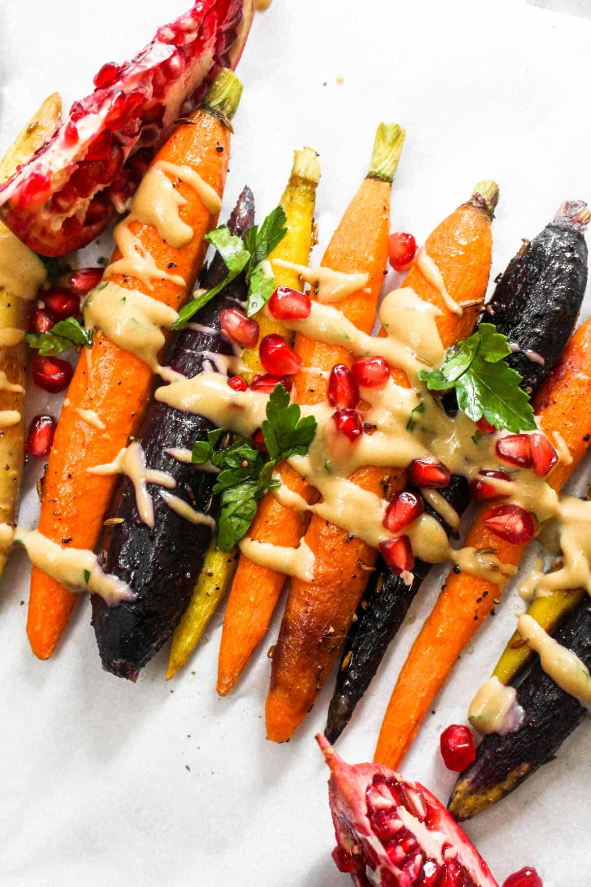 This 7 ingredient  Whole Roasted Carrots with Maple Tahini recipe is easy to make but boasts BIG flavors. This light side dish is paleo and vegan! | CatchingSeeds.com