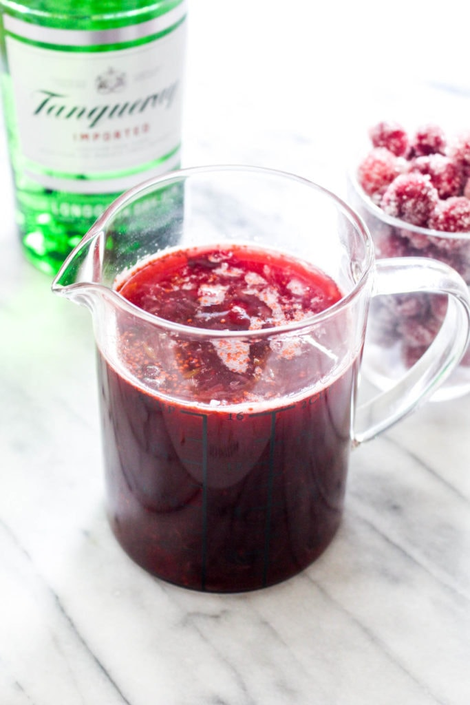 Cranberry Orange Gin Fizz is a festive cocktail filled with Holiday flavor! This easy drink recipe uses a naturally sweetened homemade cranberry sauce for a big punch of flavor. | CatchingSeeds.com