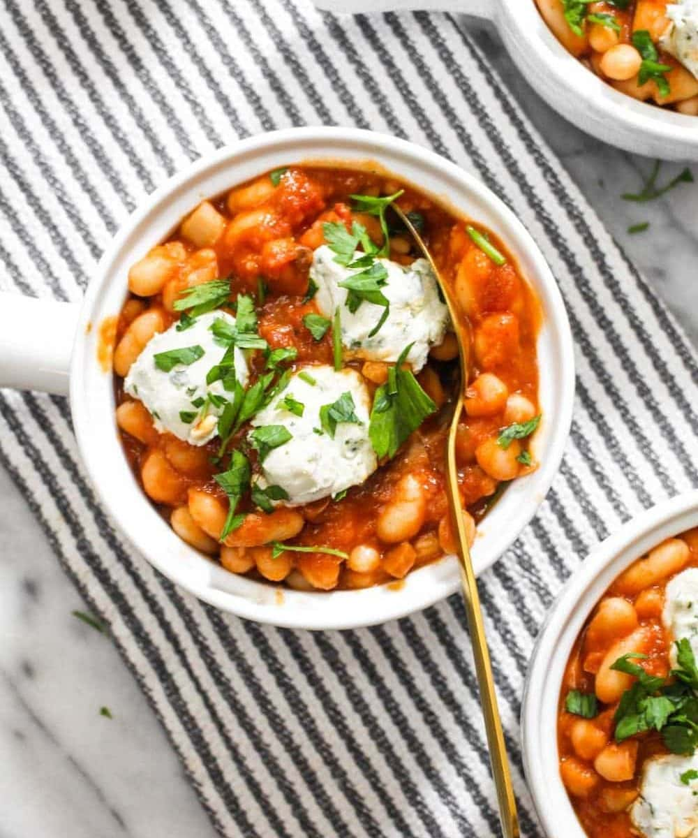 Tomato Cannellini Cassoulet with a homemade tomato sauce is bursting with comforting flavors! The DIY sauce is balanced by using canned beans to make this 8 ingredient side recipe both easy and delicious. The dollops of dairy-free cheese on top add even more rich creamy flavor. | CatchingSeeds.com