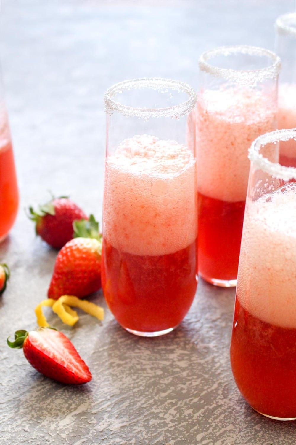 This quick and easyStrawberry French 75 cocktail is a fruity spin on the lemon flavored classic. This light drink recipe uses just 3 ingredients and is sweetened with fruit only! Its the perfect bubbly spring beverage. | CatchingSeeds.com