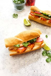 This Spicy Sriracha Tofu Banh Mi is the most flavorful sandwich you will ever eat! It is layered with Miso Lime mayo, easy Sriracha baked tofu, quick pickled veggies, and cilantro. Plus, this Vietnamese recipe is made vegan and gluten free.  CatchingSeeds.com