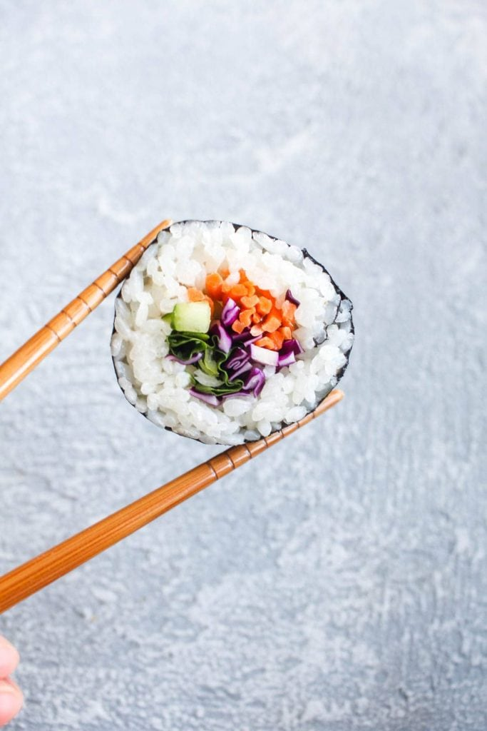 Chopsticks holding a vegetable roll with cabbage, carrot, and cucumber.