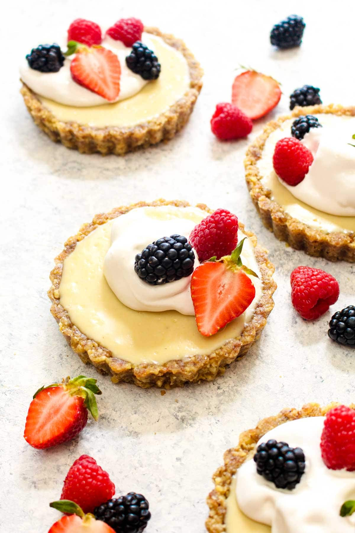 This White Chocolate Lemon Cream Tart is not only a show-stopping recipe, it is an easy 7 ingredient no bake dessert! Using natural sweeteners and whole foods, this tart is healthy, vegan, paleo, and grain free! Everyone will want to take a bite out of this lusciously creamy treat. | CatchingSeeds.com