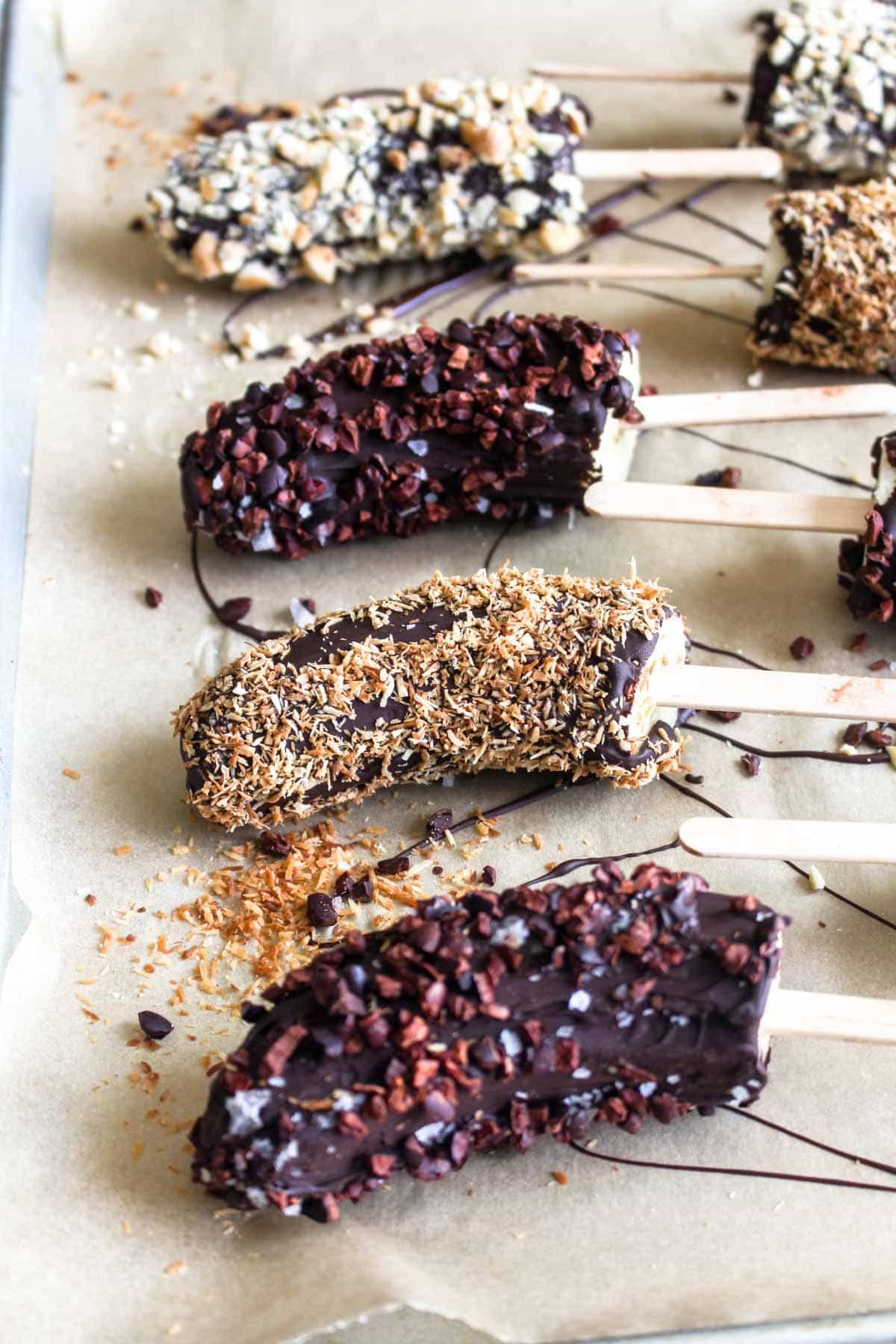 Chocolate Covered Banana Popsicles are a healthy no bake dessert! These fruit pops are covered in luscious chocolate and coated in crunchy toppings for the ultimate gluten free and vegan treat! | CatchingSeeds.com