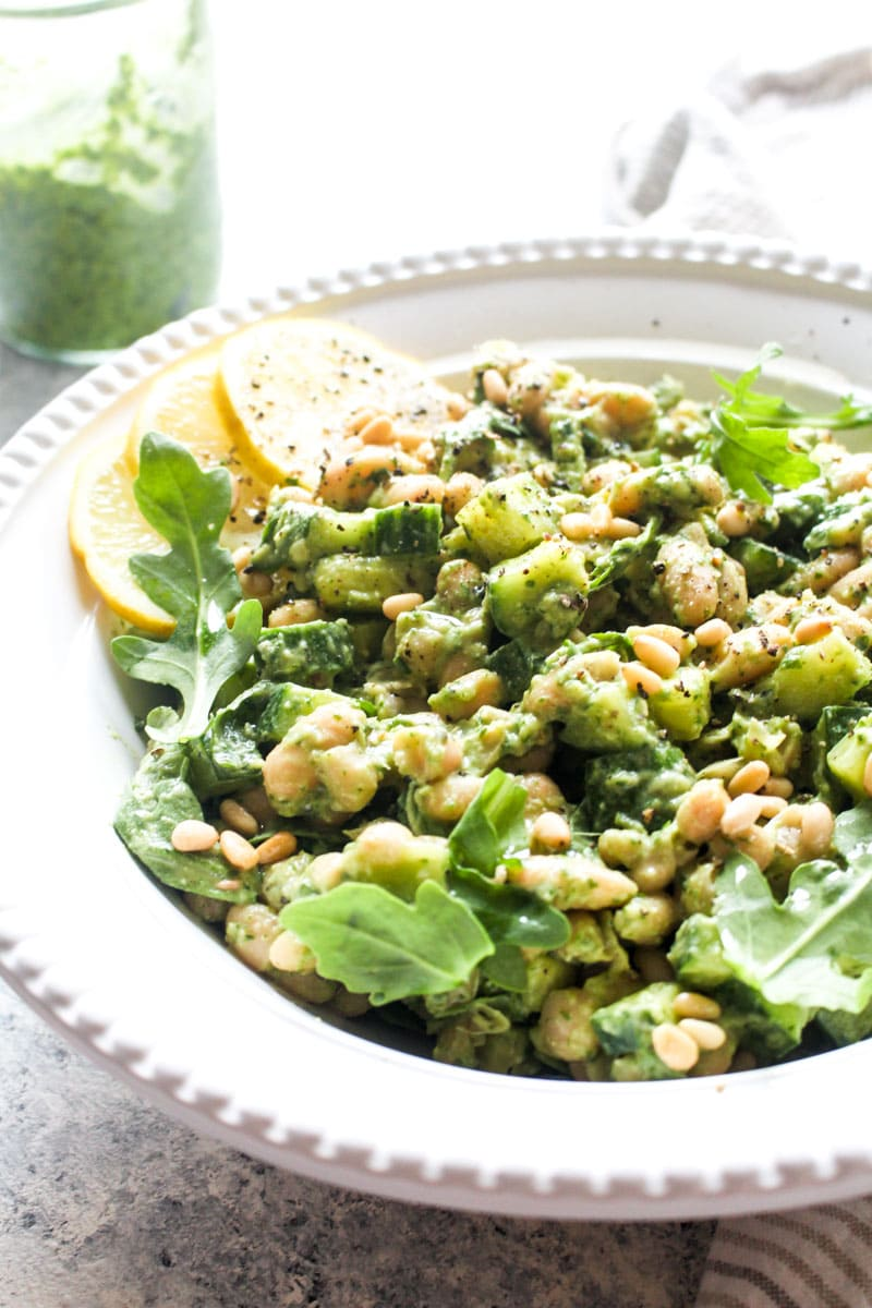This no-cook summer Pesto White Bean Salad is bursting with bright basil pesto, crunchy cucumbers, creamy beans, and peppery arugula. Perfect for hot summer nights, this gluten free and vegan dish gets even more flavorful as it sits, making it the perfect healthy picnic and potluck dish. | CatchingSeeds.com