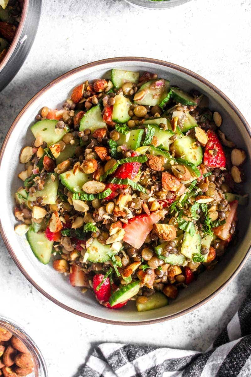 This healthy Summer Lentil Salad recipe is full of crisp cucumbers, sweet strawberries, crunchy almonds, and is marinated in a bright and herby dressing. On the table in 30 minutes! Plus this side dish is vegan, gluten free, and grain free! | CatchingSeeds.com