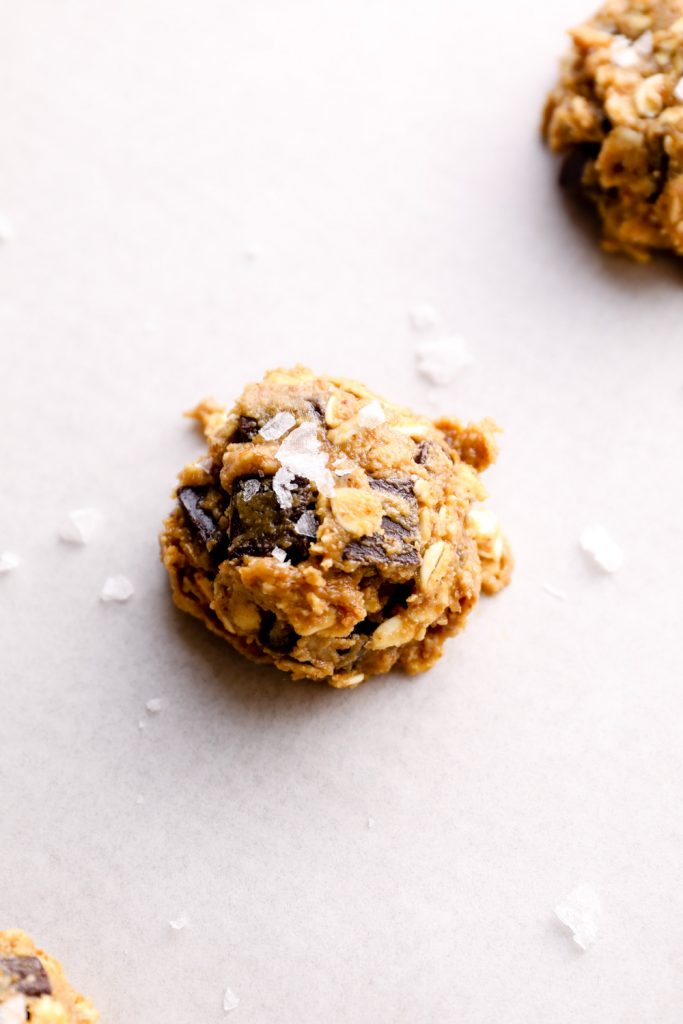 Oatmeal cookie dough rolled into balls on a sheet pan with salt flakes.