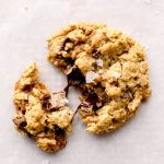 A gluten free oatmeal cookie broken with melty chocolate.