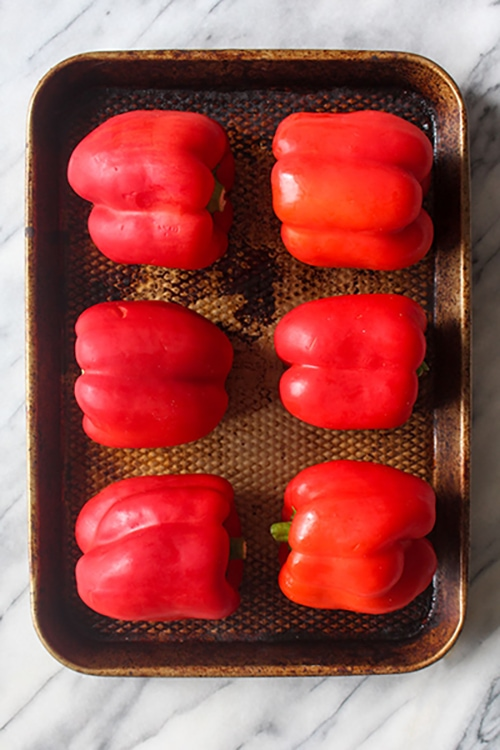 Fresh red peppers on a sheet tray.