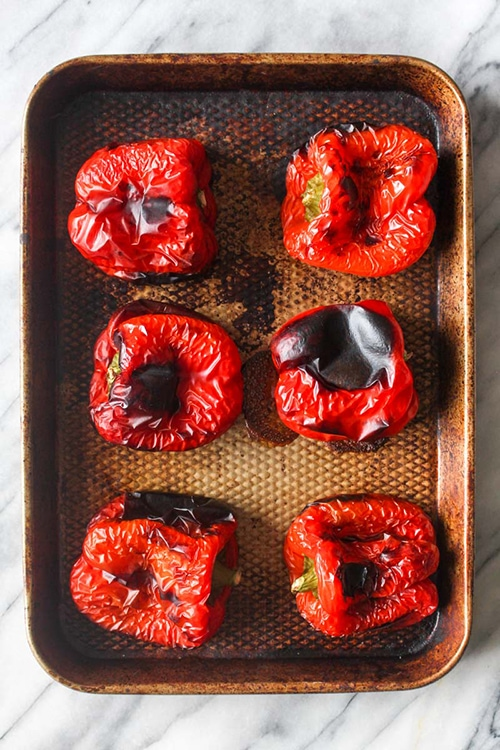 Blistered roasted red peppers on a sheet tray