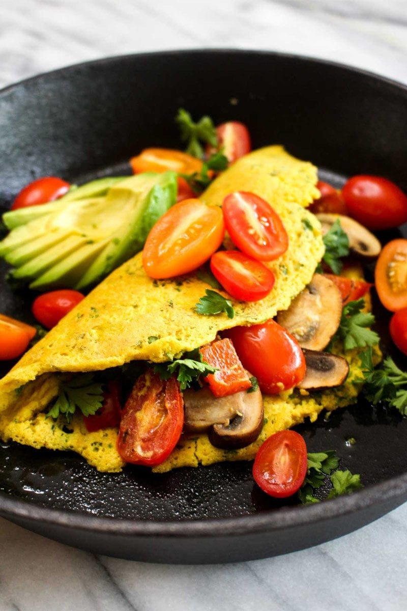 Fluffy vegan omelet filled with mushrooms and tomatoes and topped with avocado and parsley in a cast iron skillet.
