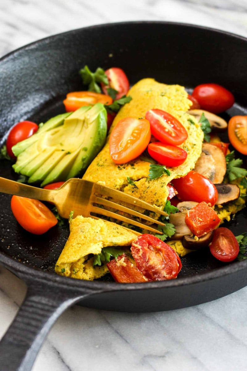 Bite being taken of a fluffy vegan omelet filled with mushrooms and tomatoes and topped with avocado and parsley in a cast iron skillet.
