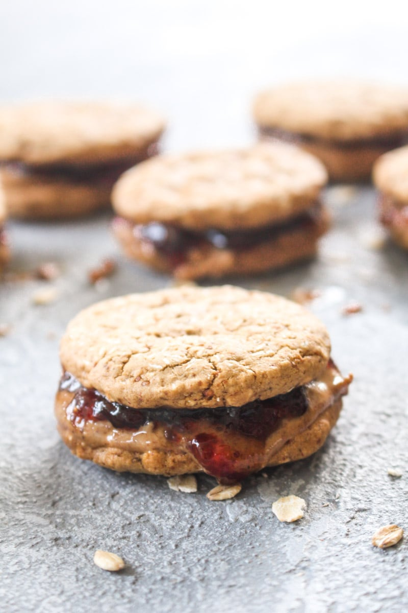 Four peanut butter and jelly sandwich cookies with raspberry jam and peanut bitter on a grey background.