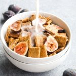 Milk being poured into a bowl of cereal with sliced figs.