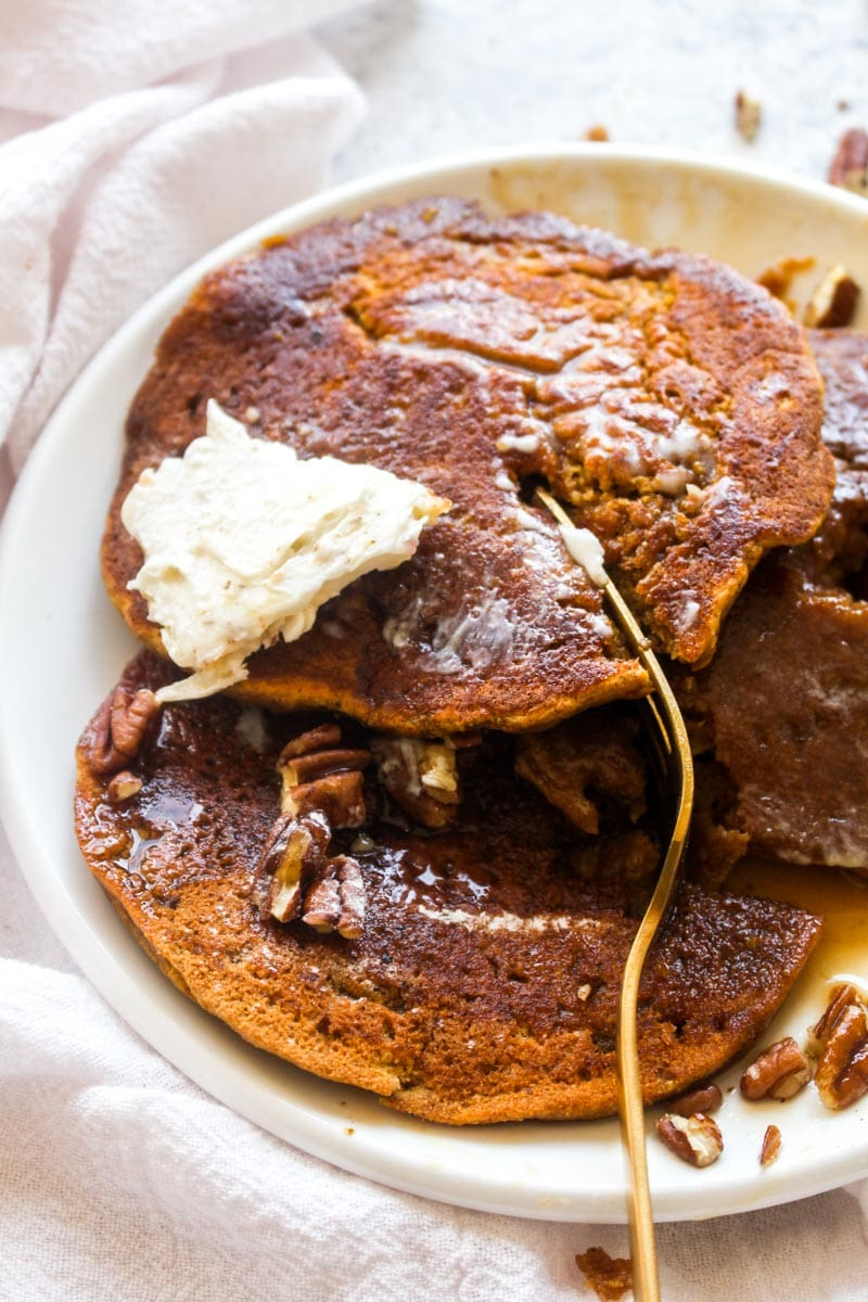 Three gluten free pumpkin pancakes on a white plate with maple syrup, pecans, and vegan butter with a gold fork cutting out a bite.