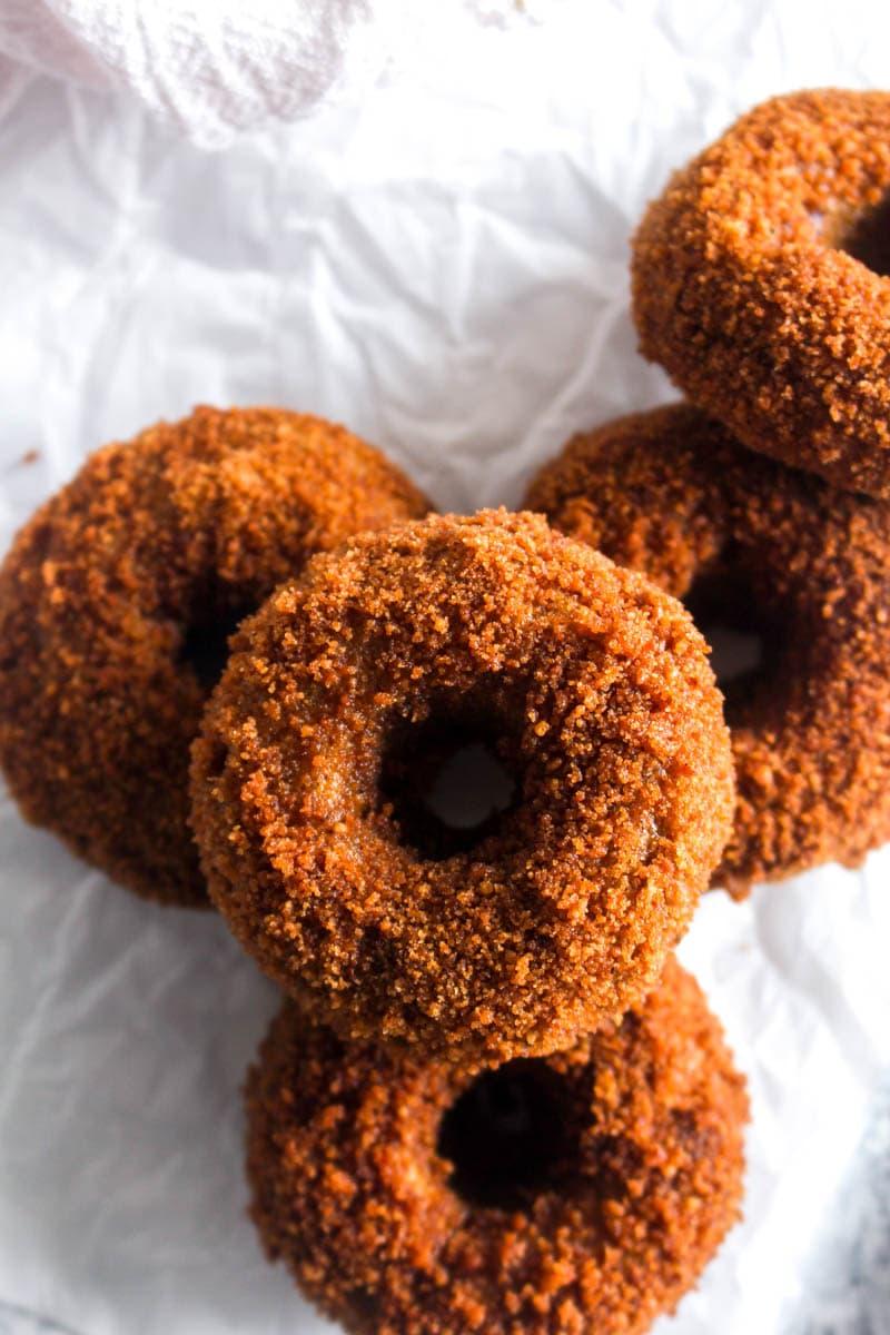 5 gluten free pumpkin spice churro donuts covered in coconut sugar on parchment paper.