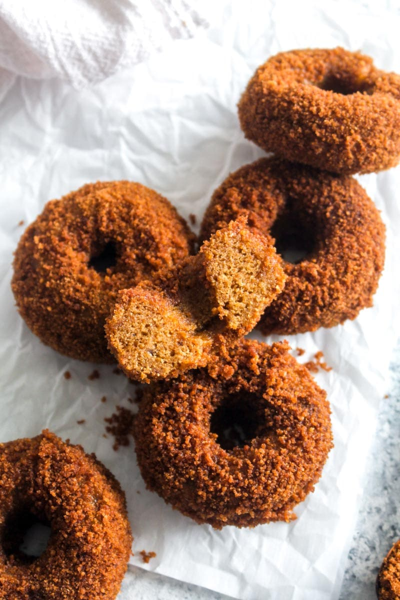 5 gluten free pumpkin spice churro donuts covered in coconut sugar on parchment paper with one donut cut in half.
