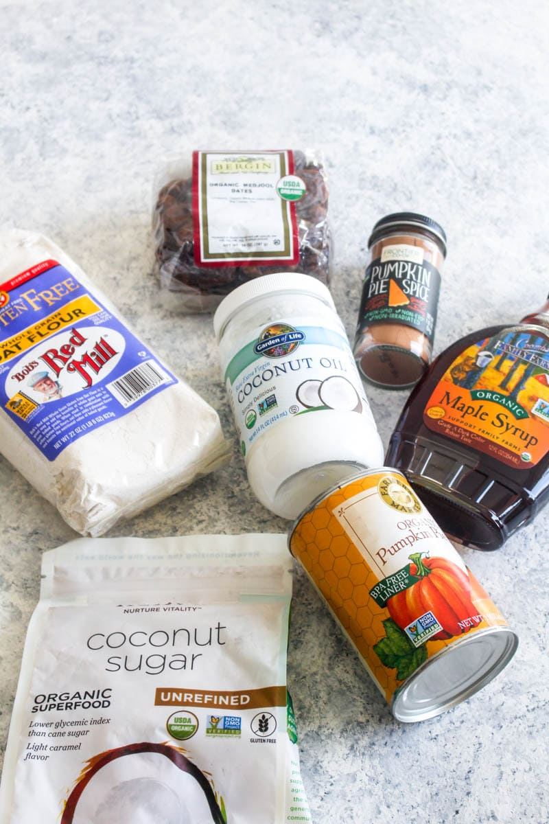 Ingredients to make pumpkin spice churro donuts like coconut oil, pumpkin pie spice, dates, oat flour, coconut sugar, canned pumpkin puree, and maple syrup.