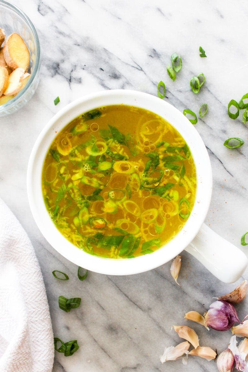 A white bowl filled with immune boosting broth with scallions, garlic, and ginger.