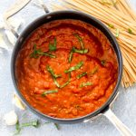 A pot of roasted red pepper pasta sauce with basil, garlic, and dry noodles.
