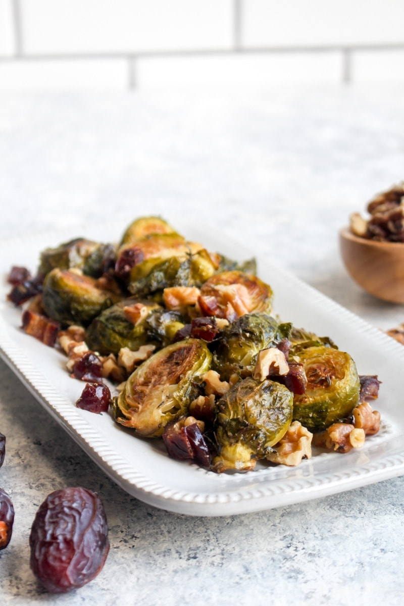 Roasted brussels sprouts on a white dish with dates and walnuts.