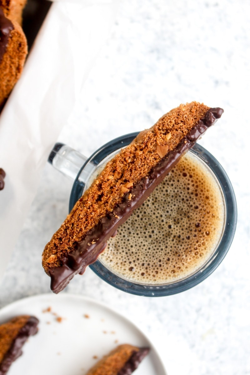 A gluten free almond biscotti resting on top of a cup of coffee on a white and grey background.