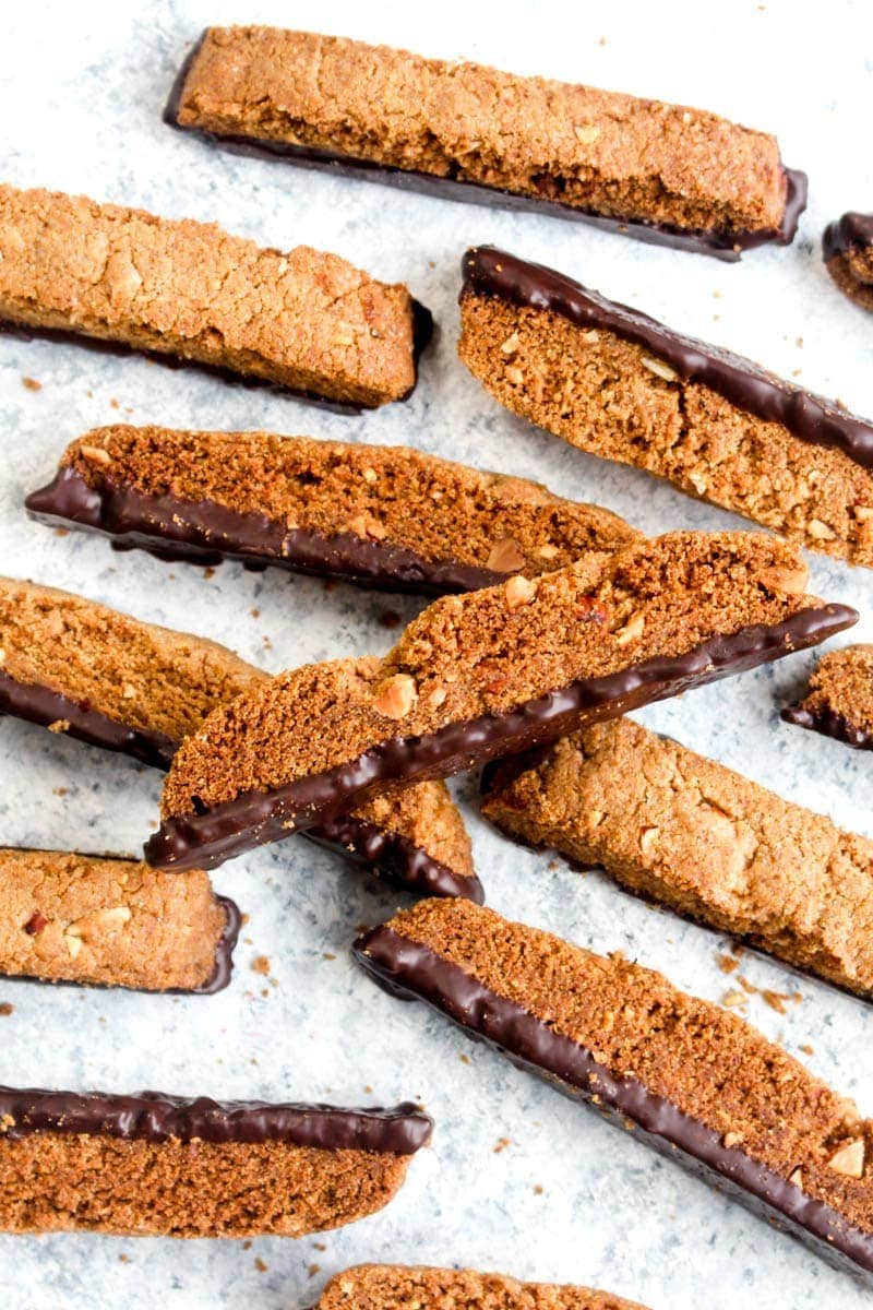 A pile of gluten free almond biscotti on a white and grey background.