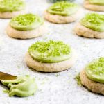 Gluten free soft frosted sugar cookies with green icing spread out on a grey background.