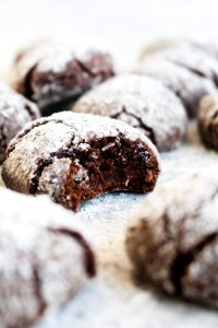 A gluten free peppermint mocha crinkle cookie with a bite out of it surrounded by other cookies.