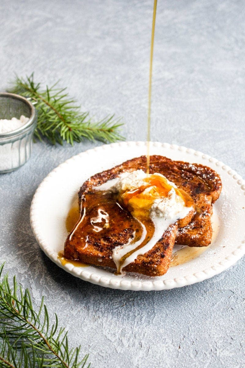 Maple syrup being poured over eggnog french toast with coconut whipped cream.