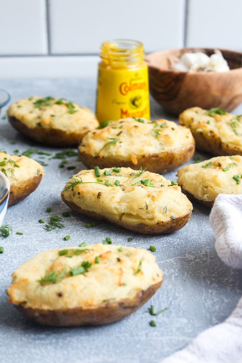 A bunch of creamy mustard twice baked potatoes on a grey background with bowls of herbs and a jar of mustard.