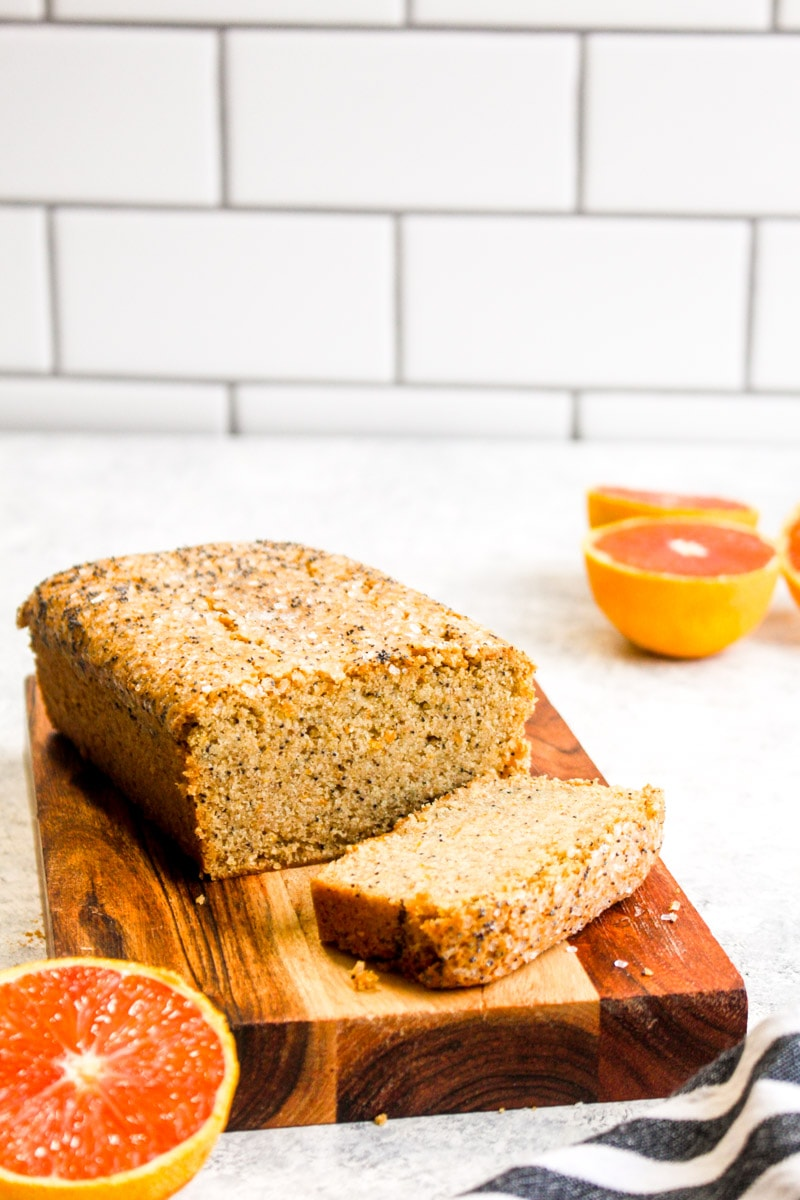 A loaf of gluten free orange poppy seed bread on a wood cutting board with one slice cut off.