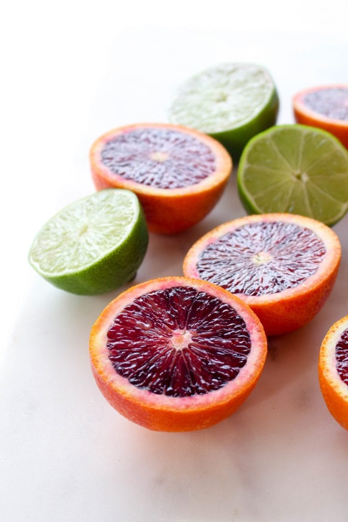 Blood oranges and limes cut in half.