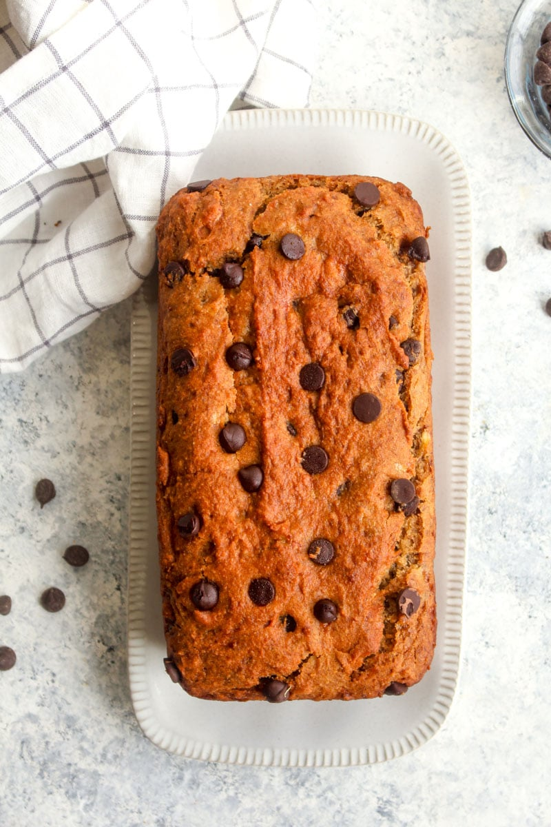 A top view of gluten free vegan chocolate chip banana bread on a white plate.