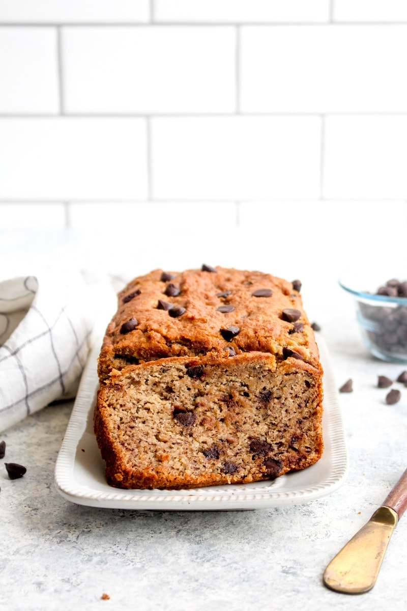 A loaf of gluten free chocolate chip banana bread with a slice cut out of it on a white plate.