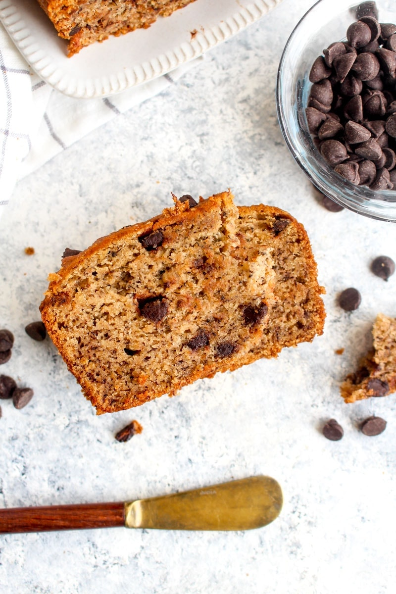 A slice of gluten free vegan chocolate chip banana bread on a grey background.