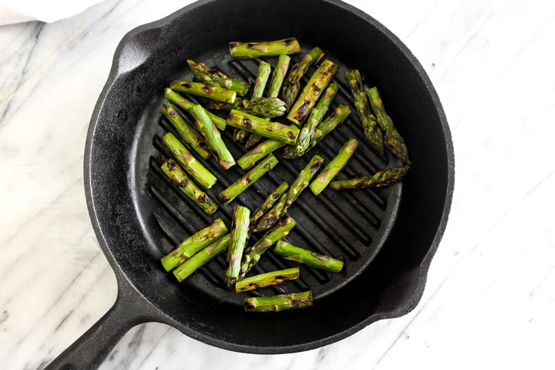 Asparagus being grilled in a cast iron grill pan.