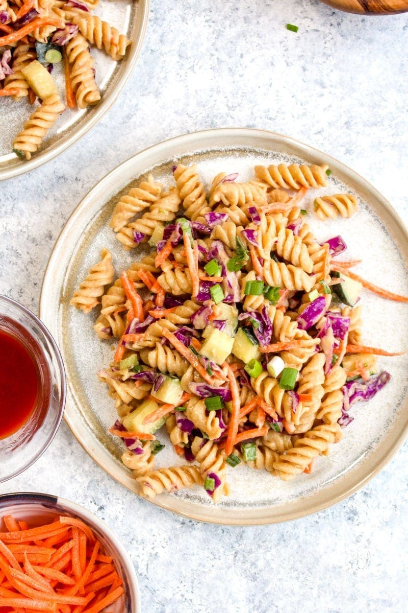 A plate full of protein packed Thai pasta salad surrounded by smaller bowls of ingredients.